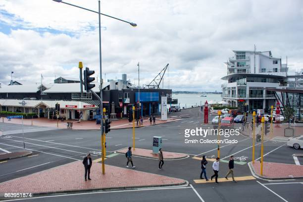 People walk through the Viaduct Harbor neighborhood of Auckland New Zealand on an overcast day with Auckland Harbor and wharves visible October 10...