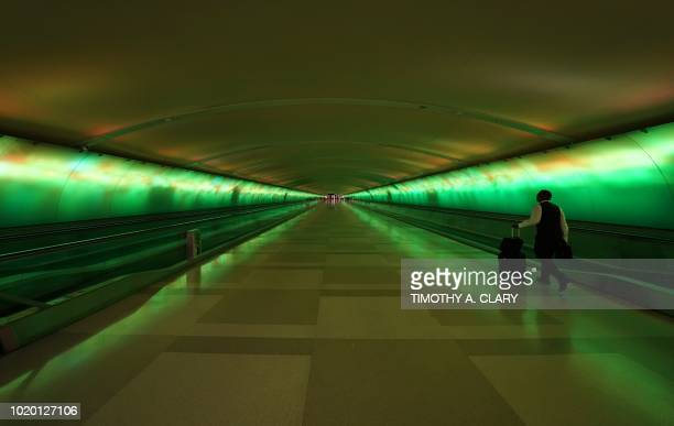 People walk through the walkway under the Detroit Metropolitan Wayne County Airport McNamara Terminal known as the 'Light Tunnel' featuring a...