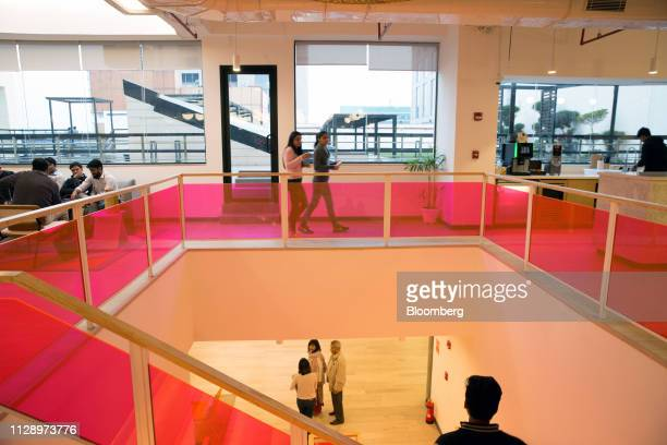 People walk through the WeWork Cos. 32nd Milestone co-working space in Gurugram, India, on Monday, Feb. 18, 2019. The New York-based co-working giant...