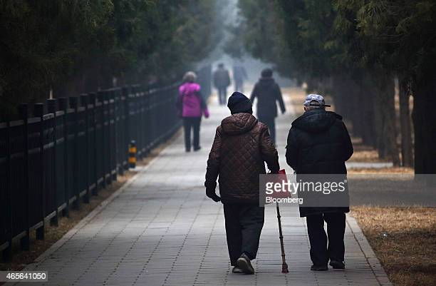 People walk through Tiantan Park in Beijing China on Sunday March 8 2015 China set the lowest economic growth target in more than 15 years and...