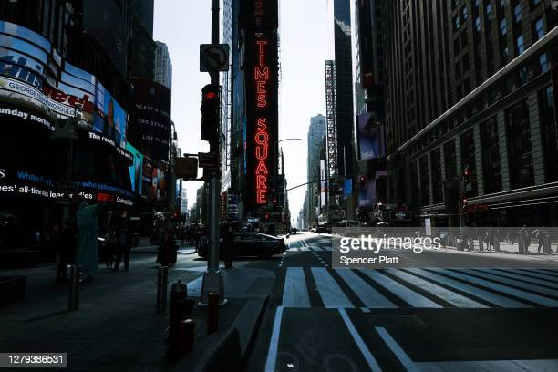 People walk through Times Square near Broadway and an empty theater district on October 9, 2020 in New York City. The Broadway League, a trade...