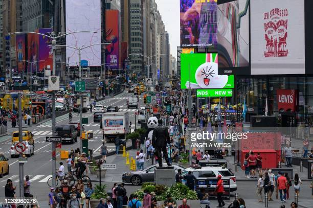 People walk through Times Square on July 13, 2021 in New York City. - Stock markets were slightly softer on news of the biggest jump in US inflation...