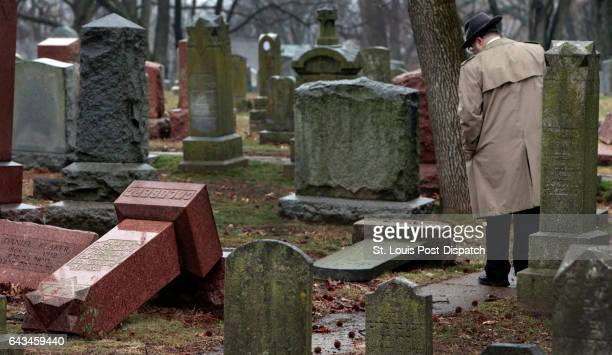 People walk through toppled graves at Chesed Shel Emeth Cemetery in University City on Tuesday Feb 21 2017 where almost 200 gravestones were...