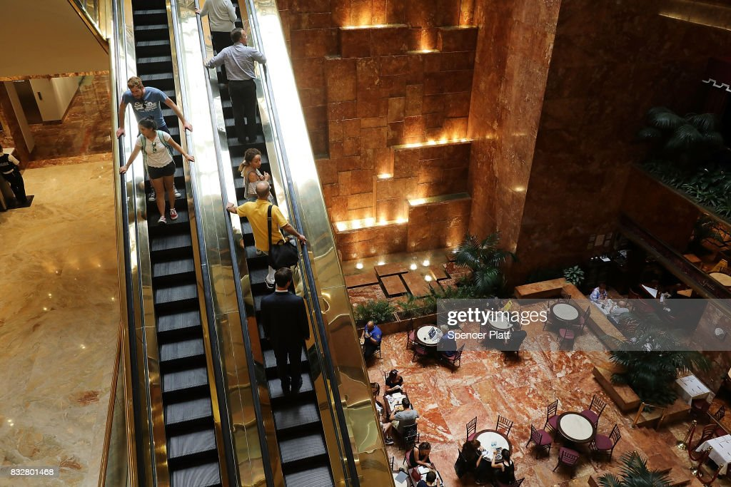 People walk through Trump Tower after it re-opened following the departure of US President Donald Trump on August 16, 2017 in New York City. President Trump arrived at his residency at the tower on Monday evening, his first trip back to Trump Tower since the inauguration.