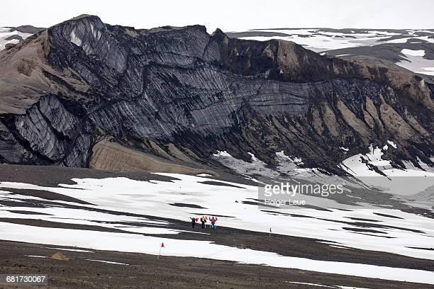 People walk through volcanic landscape