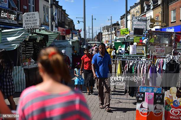 People walk through Walthamstow market on August 9 2016 in London England Walthamstow Market in north east London is believed to be the longest daily...
