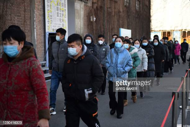 People walk to a COVID-19 coronavirus vaccine center in Beijing on January 4 as China races to innoculate millions before the Chinese New Year mass...