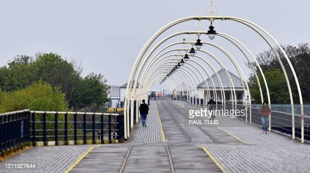 People walk to and from the shut gates leading to the closed-down pier in Southport, north west England, on April 26 as life in Britain continues...