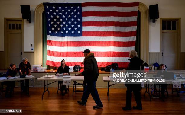 People walk to collect their ballots before voting in the Virginia Democratic primary at the Hillsboro Old Stone School in Hillsboro Virginia on...