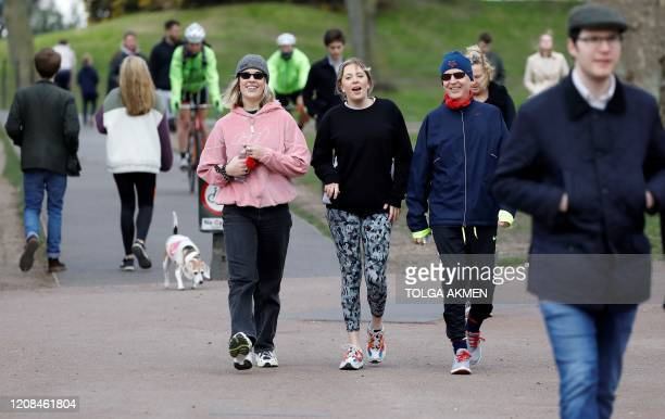 People walk to get their daily exercise allowance in Battersea Park in London on March 28 as life in Britain continues during the nationwide lockdown...