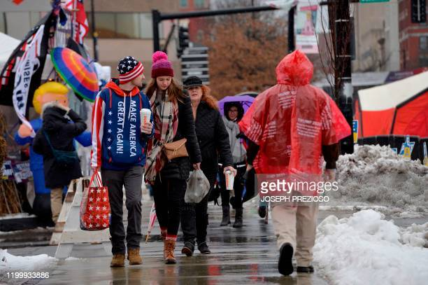 People walk to line up in the rain and icy weather outside the SNHU arena hours ahead of President Donald Trump's rally in Manchester New Hampshire...