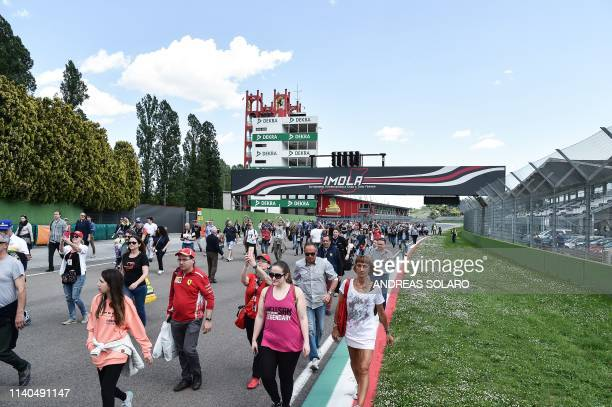 """People walk to reach the curve of the """"Tamburello"""" track to take part in a ceremony marking the 25th anniversary of the death of Brazilian's F1..."""