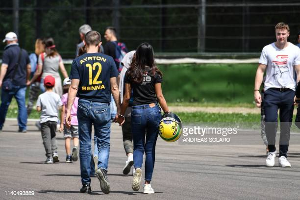 People walk to reach the curve of the Tamburello track to take part in a ceremony marking the 25th anniversary of the death of Brazilian's F1 driver...
