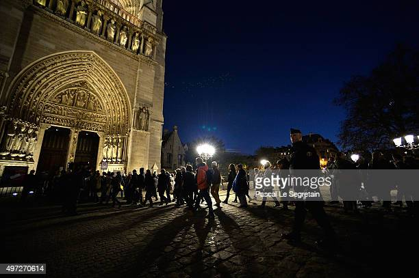 People walk to the Notre Dame Cathedral ahead of a ceremony to the victims of the friday's terrorist attacks on November 15 2015 in Paris France As...