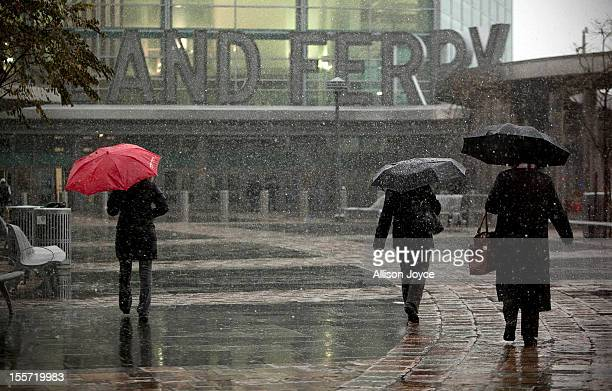 People walk to the Staten Island Ferry during a Nor'easter also known as a northeaster storm November 7 2012 in New York City The storm will bring...