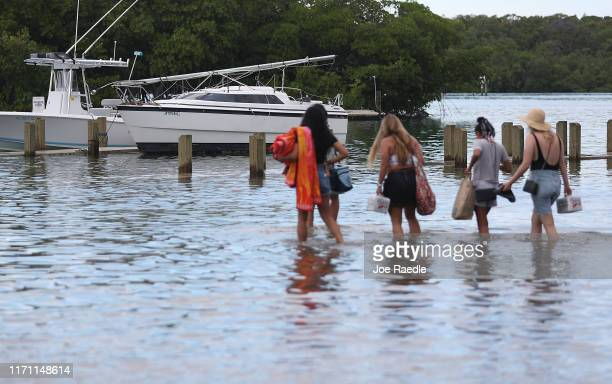 People walk to their boat through a flooded parking lot at the Haulover Marine Center before the arrival of Hurricane Dorian on August 30 2019 in...
