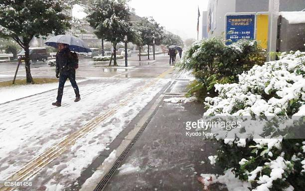 People walk to their offices in Tachikawa Tokyo on the morning of Nov 24 the day when the Japanese capital had snowfall in November for the first...