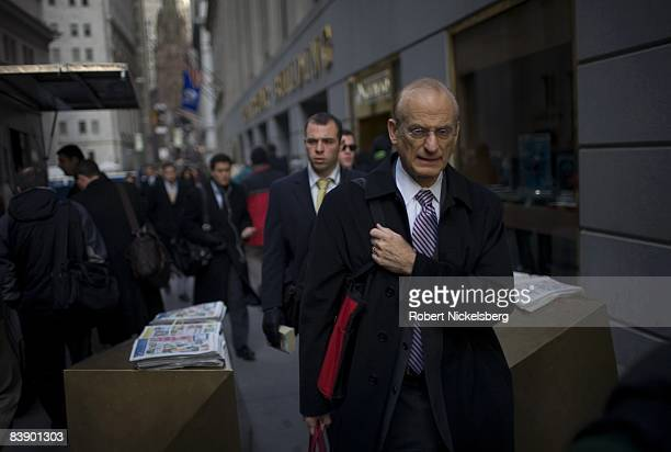People walk to work along Wall Street near the New York Stock Exchange in the financial district of New York on November 24 2008 in New York City...