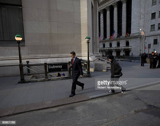People walk to work along Wall Street near the New York Stock Exchange right in the financial district of New York on November 24 2008 in New York...