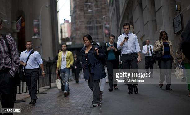 People walk to work on Wall Street near the New York Stock Exchange June 5 2012 in New York City