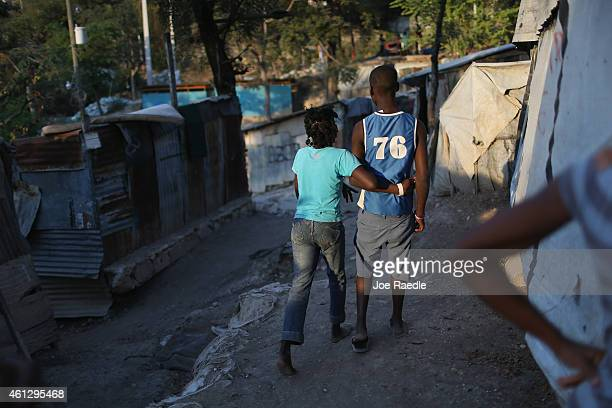 People walk together through the camp where they live in homes made out of tin and tarps built over the land where their homes once stood before a...