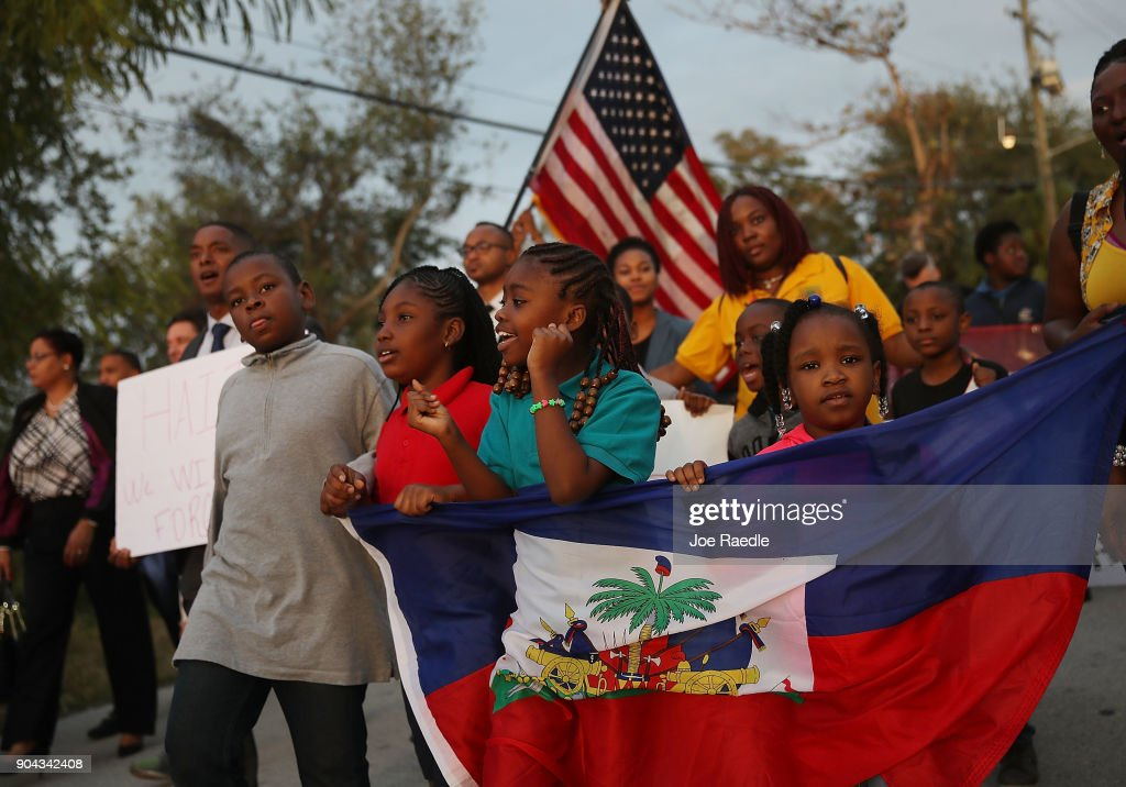 People walk together to mark the 8th anniversary of the massive earthquake in Haiti and to condemn President Donald Trump's reported statement about immigrants from Haiti, Africa and El Salvador on January 12, 2018 in Miami, Florida. President Trump is reported to have called those places 'shithole countries' whose inhabitants are not desirable for U.S. immigration.