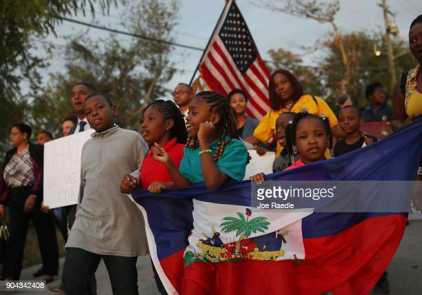 People walk together to mark the 8th anniversary of the massive earthquake in Haiti and to condemn President Donald Trump's reported statement about...