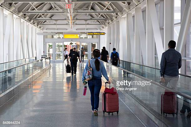 People walk toward the departures terminal at John F Kennedy International Airport June 30 2016 in the Queens borough of New York City Following...