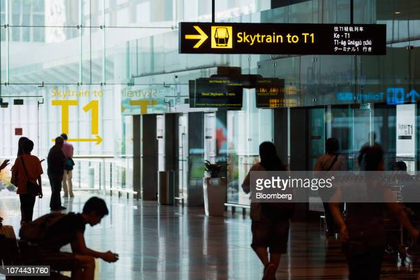 People walk towards a Changi Airport Skytrain station to Terminal 1 at Terminal 3 of Changi Airport in Singapore on Thursday Dec 13 2018...