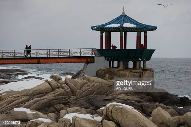 People walk towards a coastal pagoda at the eastern port city of Sockcho on February 19, 2014. A group of 82 elderly, specially-selected South...