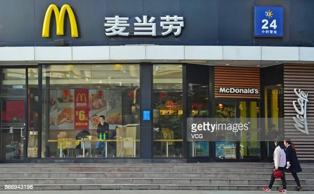 People walk towards a McDonald's restaurant on October 27, 2017 in Zhengzhou, China. McDonald's China has changed its company name from Maidanglao, a...