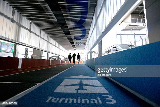 People walk towards Terminal 3 of Narita Airport in Narita Japan on Wednesday March 25 2015 The airport operator Narita International Airport Corp...