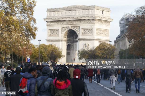 People walk towards the Arc de Triomphe as they take part in a march against 'slavery in Libya' on November 18 2017 in Paris / AFP PHOTO / GEOFFROY...