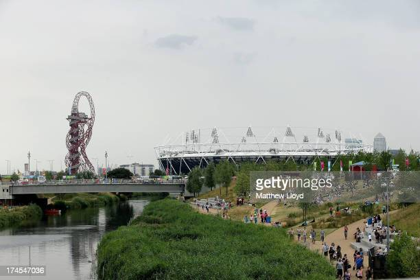 People walk towards the Olympic stadium as they explore the Queen Elizabeth Olympic Park during the Open East Festival on July 27 2013 in London...