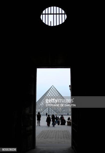 People walk towards the the Louvre Pyramid in Paris on February 19 2018 SAKUTIN