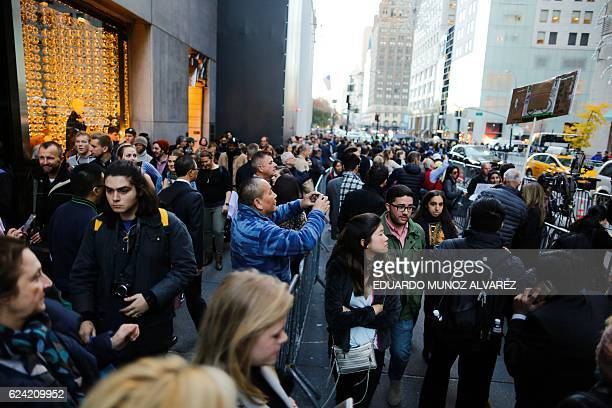 People walk trough 5th Avenue near Trump Tower after the street was closed to foot traffic by police with barricades and officers at the entrance to...