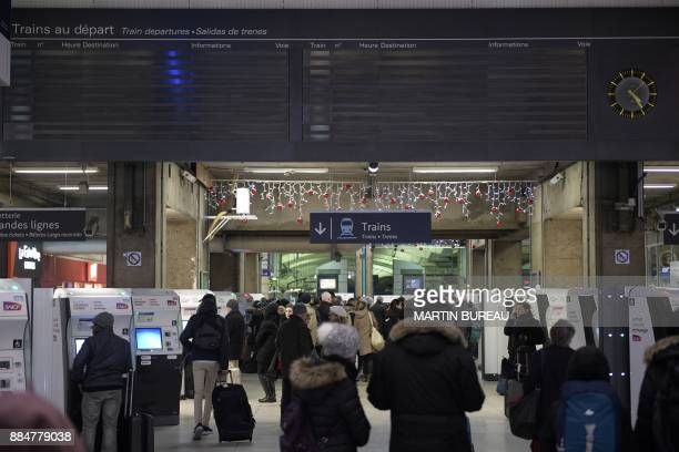 People walk under a blank departures information board inside the Montparnasse train station in Paris on December 3 as rail traffic was interrupted...