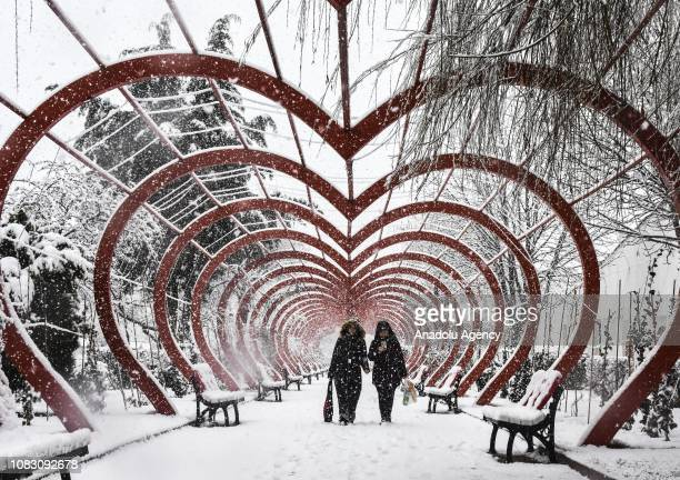 People walk under a heart shaped steel at a park during snowfall in Bozuyuk district of Bilecik Turkey on January 15 2019