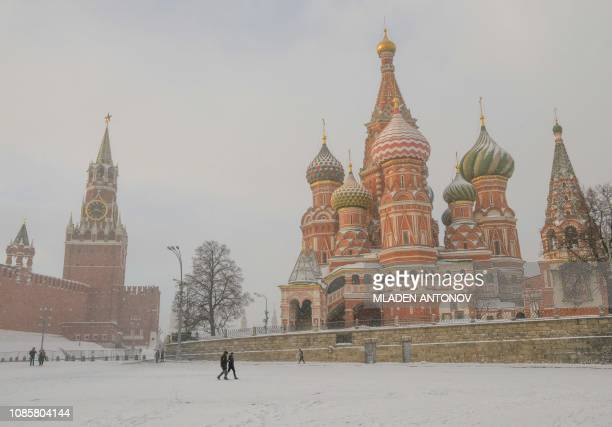 People walk under a heavy snowfall in front of St Basil's Cathedral and the Kremlin in Moscow on January 21 2019 In a rare event Moscow witnessed a...