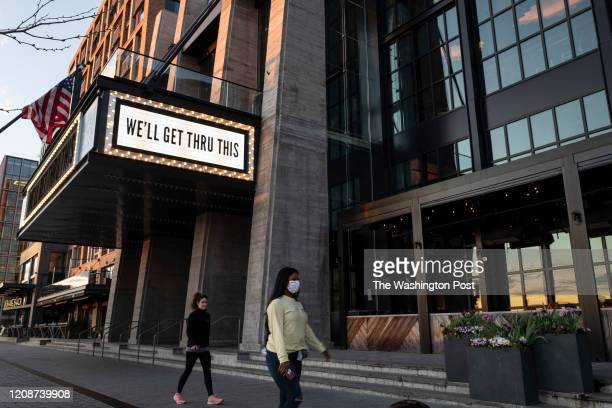 People walk under a hopeful sign on the Anthem's marquis in SW Washington DC on March 30 2020 The nation's capital has taken on a different air as...