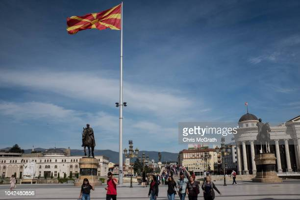 People walk under a larg Macedonian flag on September 28 2018 in Skopje Macedonia Macedonians will go to the polls Sunday to vote in a referendum to...