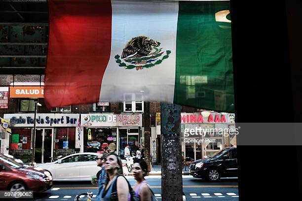 People walk under a Mexican flag in the ethnically diverse neighborhood of Queens on August 29 2016 in New York City Queens County is one of the five...