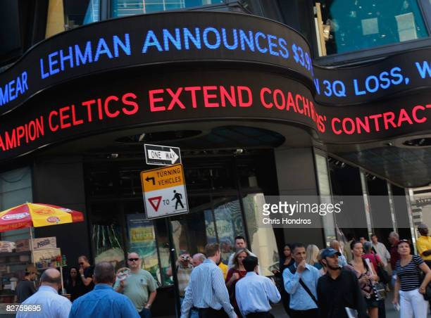 People walk under a ticker sign announcing Lehman Brothers financial losses September 10, 2008 in New York. Lehman Brothers plans to sell a majority...