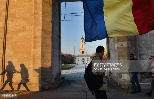 People walk under a triumph arch next to flag of Moldova in Chisinau Moldova on March 20 2014 The president of the former Soviet republic of Moldova...
