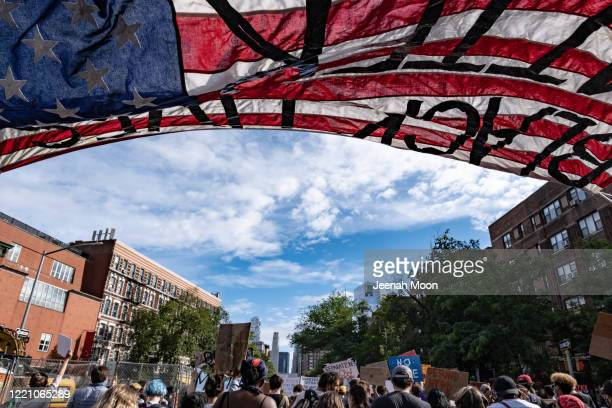 People walk under an American flag reading Black Lives Matter during a protest on June 18 2020 in New York City Protesters plan to mark Juneteenth...