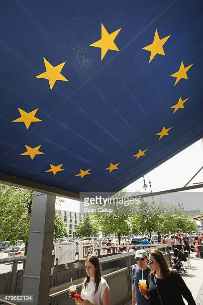 People walk under an awning decorated as the flag of the European Union the day after a majority of people voted 'no' in the Greek referendum on July...