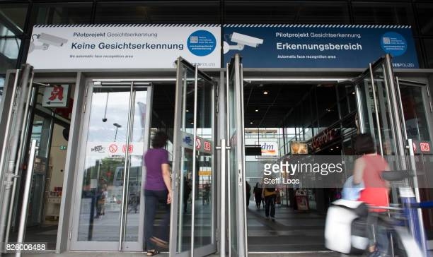 People walk under an information sign which make passersby aware of a facial recognition technology test at Berlin Suedkreuz station on August 3 2017...