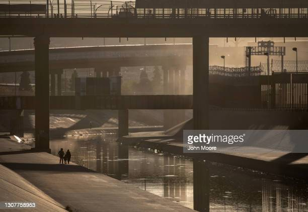 People walk under an international bridge along the Mexican side of the Rio Grande while scouting crossing points on March 17, 2021 in Ciudad Juarez,...