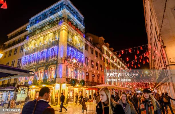 People walk under Christmas and New Year color changing illuminations in Rua Augusta on December 11, 2019 in Lisbon, Portugal. The city shows every...
