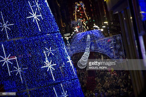 People walk under christmas lights at the Puerta del Sol in Vigo northwestern Spain on December 7 2014 AFP PHOTO/ MIGUEL RIOPA